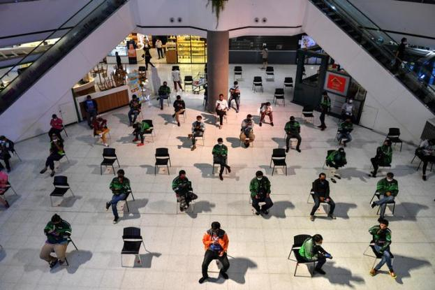 Staff of food delivery companies sit on social distancing chairs due to coronavirus disease (COVID-19) outbreak, as they wait for their costumers' orders at a department store in Bangkok